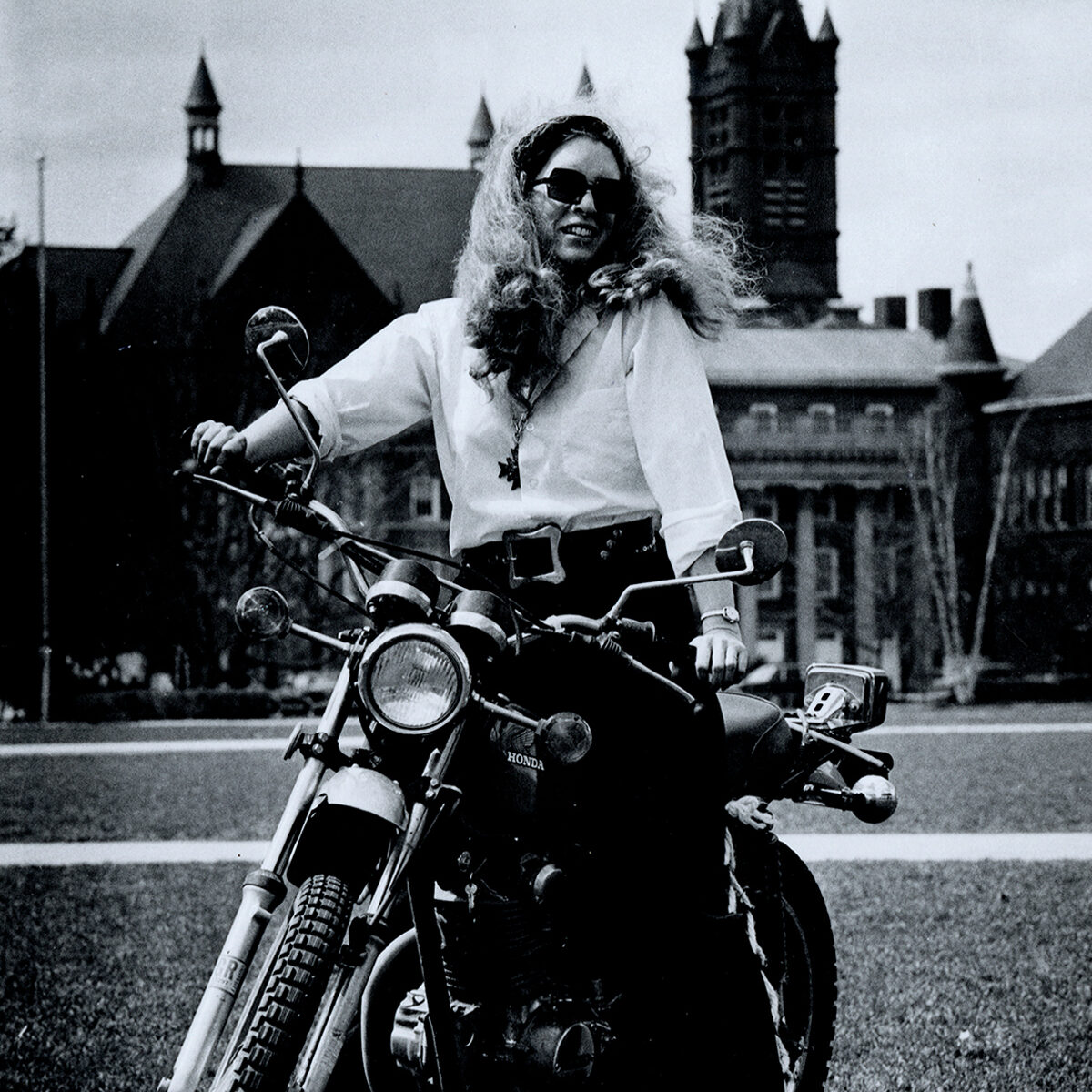 Dr. Sarah Sally Short on motorcycle on the campus of Syracuse University